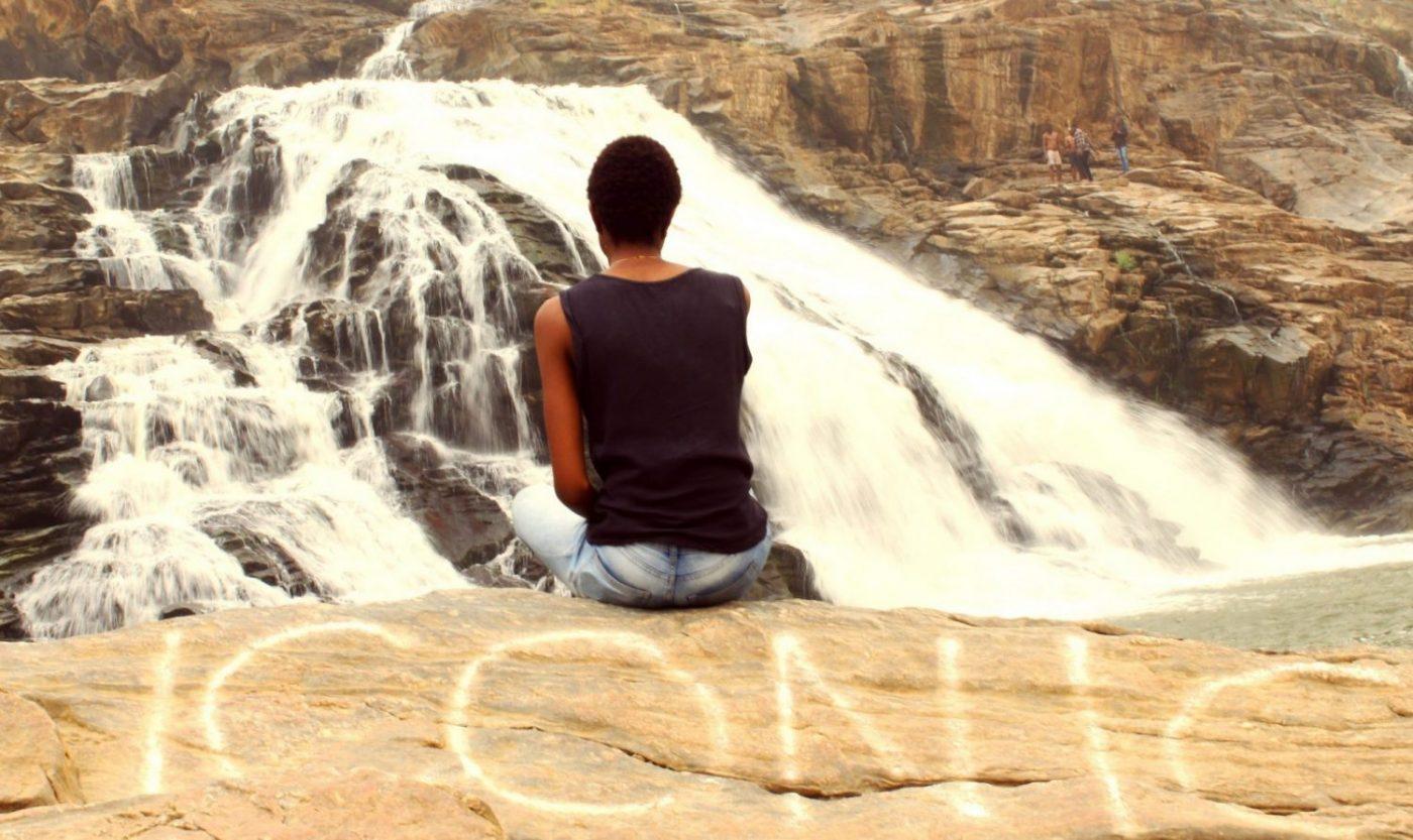 sitting-on-nigeria-waterfall-cliff